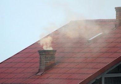 Widok komina na dachu budynku emitującego gęsty dym.
