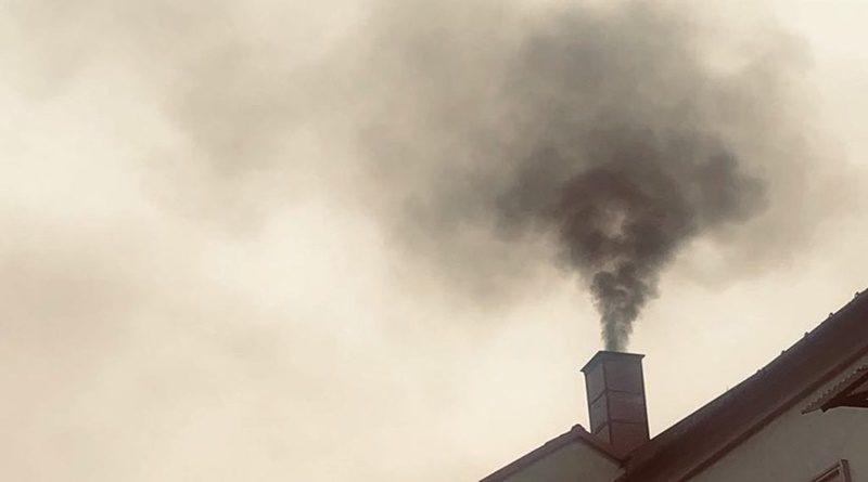 Zdjęcie pokazuje komin budynku, z którego bydobywa się czarny słup dymu.
